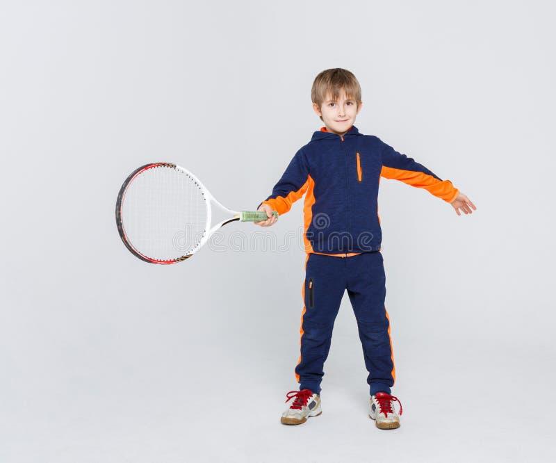 Weinig leuke tennisspeler in sportkleding met racket bij studioachtergrond stock fotografie
