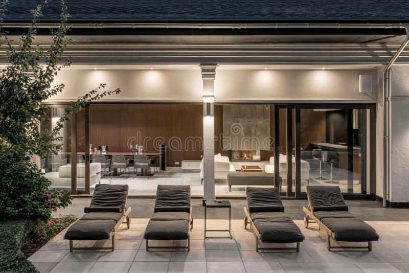 Weinig ligstoelen op betegeld terras van lichtgevende villa stock afbeelding
