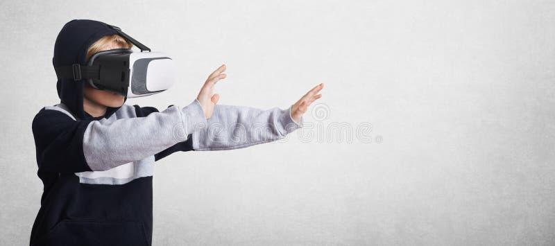 Weinig mannelijk kind in sweatshirt en virtuele gebaren van werkelijkheidsglazen met handen, rekken hen uit vooruit, in wisselwer royalty-vrije stock afbeelding