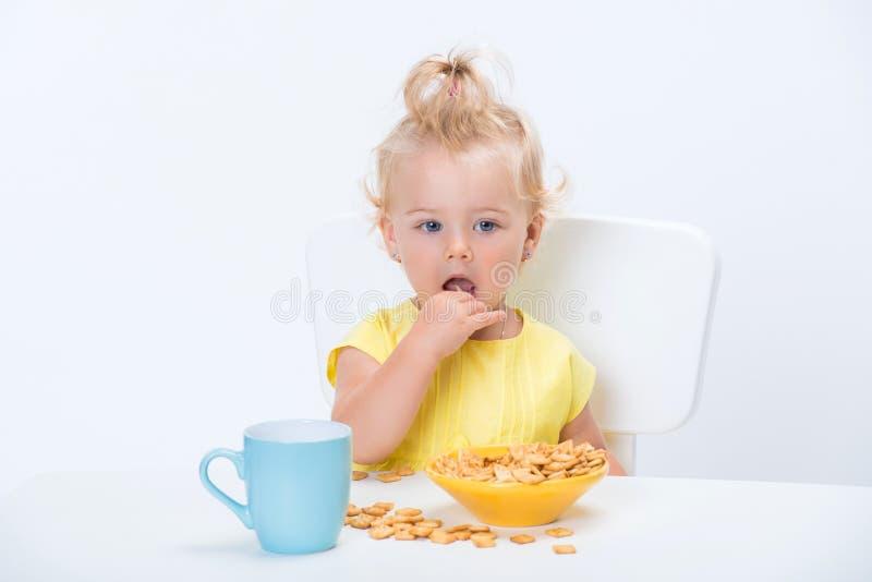 Weinig meisje van de blondebaby 1 éénjarige in gele t-shirt die graangewas eten schilfert en een kop van melkthee drinken bij de  stock afbeelding