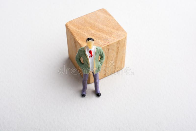 Weinig mensenbeeldje naast een houten kubus royalty-vrije stock afbeelding