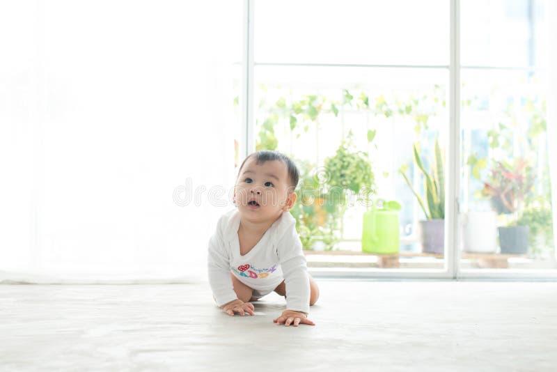 Weinig mooi babymeisje die op de vloer thuis kruipen stock foto