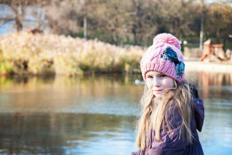 Weinig mooi blondemeisje in roze hoed op achtergrond van herfstmeer stock foto