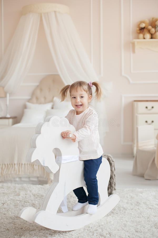 Weinig mooi glimlachend meisje op het houten stuk speelgoed paard binnen de ruimte van een kind royalty-vrije stock foto's