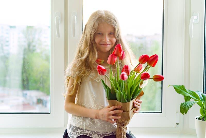 Weinig mooi kindmeisje met boeket van rode tulpen bloeit thuis dichtbij het venster, heden voor moederdag Gift, verrassing, stock foto's