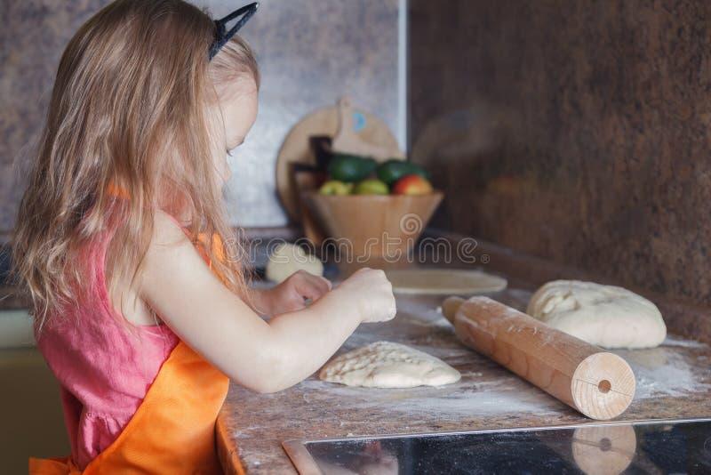 Weinig mooi leuk meisje in oranje schort die en eigengemaakte pizza glimlachen maken, rolt thuis de deegkeuken Concepten gelukkig stock afbeelding