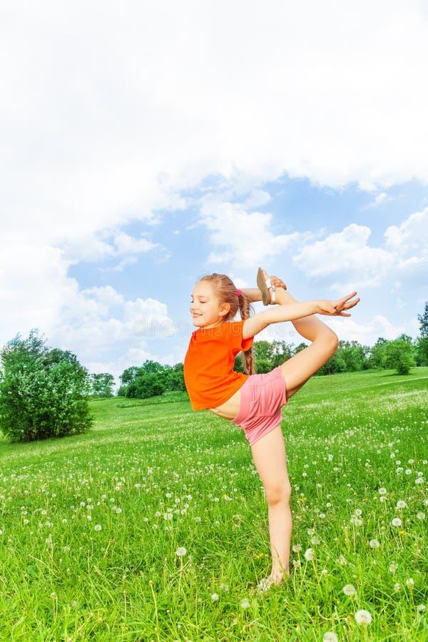 Weinig mooi meisje die gymnastiek op een gras doen royalty-vrije stock fotografie