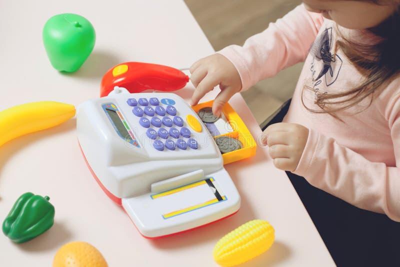 Weinig mooi meisje die met stuk speelgoed opslag spelen Onderwijsproces stock fotografie