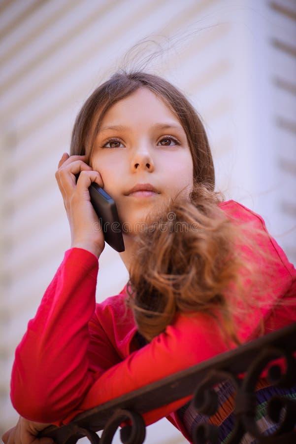 Weinig mooi meisje die op celtelefoon spreken royalty-vrije stock foto's