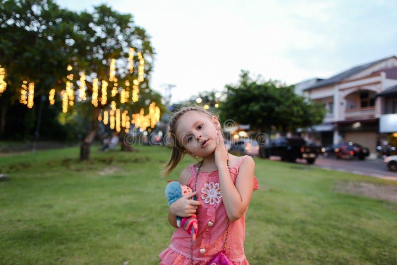 Weinig mooi meisje die roze kleding met stuk speelgoed dragen die zich op gazon in stad bevinden stock foto's