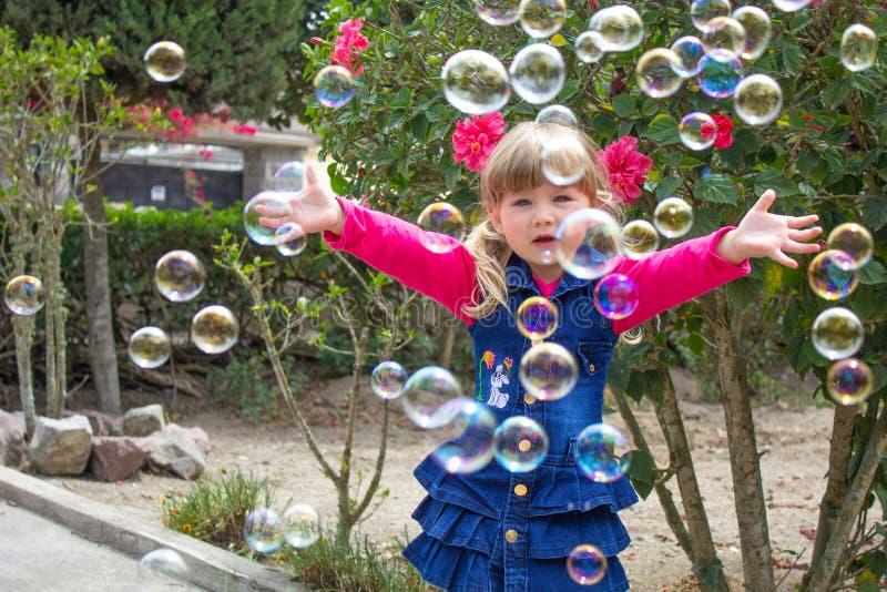 Weinig mooi meisje loopt met een zacht stuk speelgoed in hun handen op openlucht Meisje het spelen met zeepbels in de tuin stock fotografie