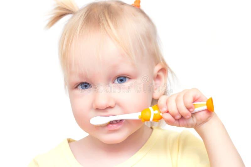 Weinig mooi meisje met blauwe ogen en vlechten borstelt haar tanden op een witte achtergrond, close-up, isoleert stock foto's