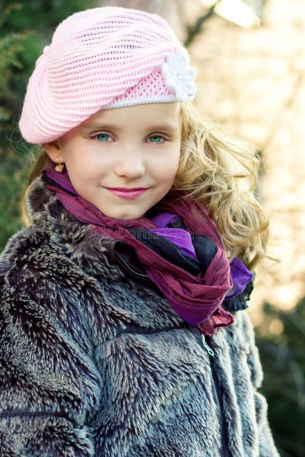 Weinig mooi meisje met blauwe ogen in roze hoed die zich op de straat bevinden royalty-vrije stock foto's