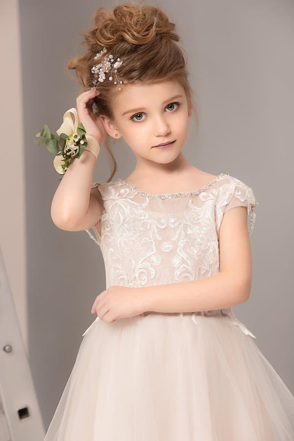Weinig mooi meisje met bloemen kleedde zich in huwelijkskleding royalty-vrije stock foto's