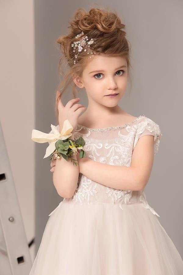 Weinig mooi meisje met bloemen kleedde zich in huwelijkskleding stock afbeelding