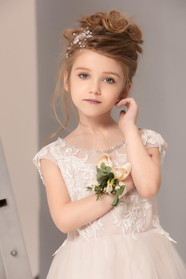 Weinig mooi meisje met bloemen kleedde zich in huwelijkskleding stock foto's