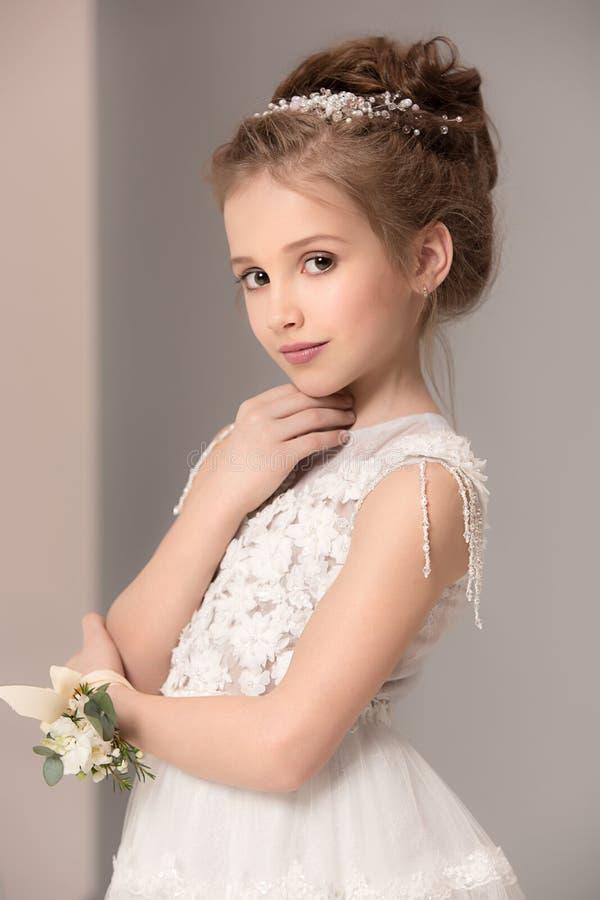 Weinig mooi meisje met bloemen kleedde zich in huwelijkskleding royalty-vrije stock afbeelding