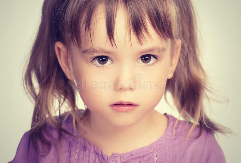 Weinig mooi meisje met droevige ogen stock afbeelding