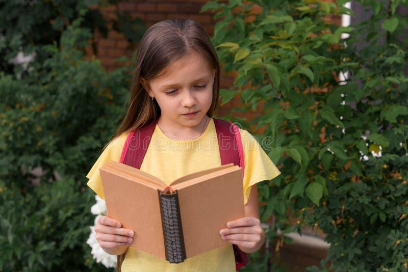 weinig mooi meisje met een rugzak die een boek houden en op de achtergrond van een bakstenen muur en groene struiken lezen stock afbeelding