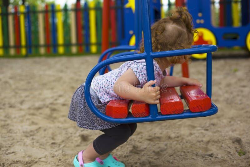 Weinig mooi meisje wordt gespeeld op de speelplaats stock afbeelding