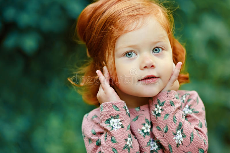 Weinig mooi roodharig meisje die, in samenvatting gelukkig glimlachen stock foto's