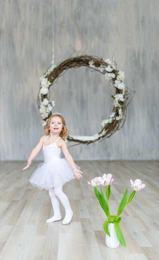 Weinig mooie ballerina in witte kleding en tulpen stelt in een mooie studio stock foto's