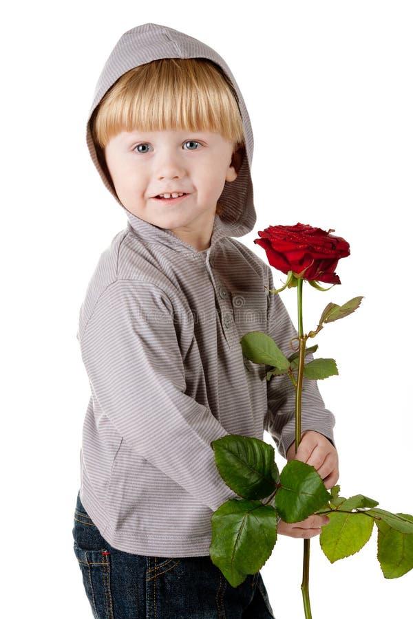Weinig mooie jongen met rood nam toe stock foto