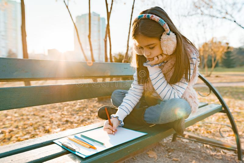 Weinig mooie kunstenaarstekening met kleurpotloden, meisjeszitting op een bank in zonnig de herfstpark, gouden uur royalty-vrije stock afbeelding