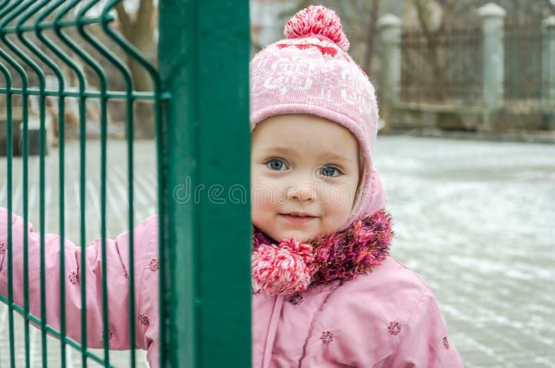 Weinig mooie meisjesbaby achter de omheining, net sloot in een GLB en een jasje met droevige emotie op zijn gezicht stock afbeeldingen