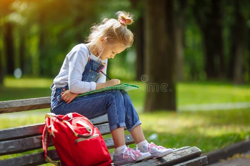 Weinig mooie tekening van het schoolmeisje met kleurpotloden, zitting op een bank in zonnig park stock afbeelding