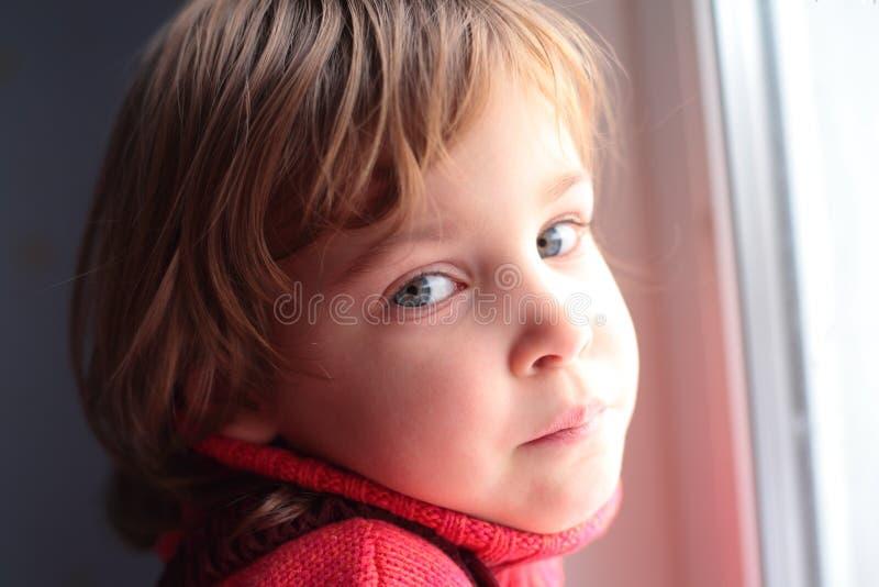 Weinig nadenkend meisje bij venster stock fotografie
