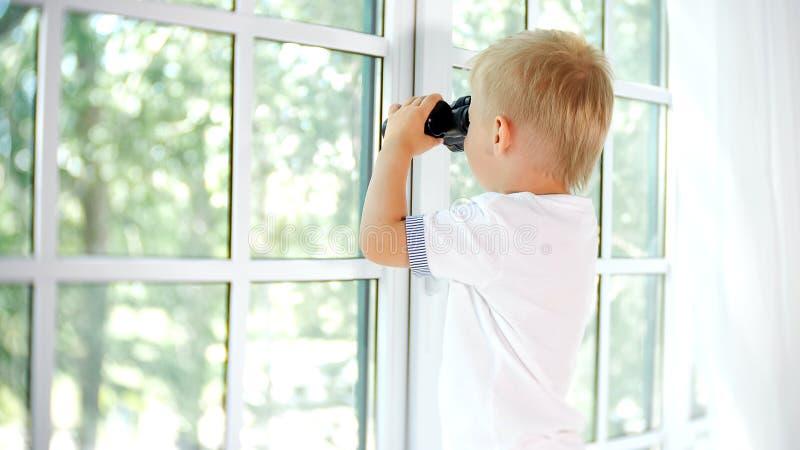 Weinig nieuwsgierige jongen die in venster met binoculair kijken royalty-vrije stock afbeeldingen