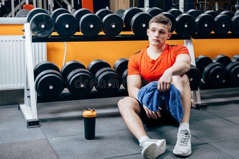 Weinig onderbreking De knappe jonge mens in sportkleding ontspant na opleiding in gymnastiek, zit en bekijkt venster royalty-vrije stock afbeelding