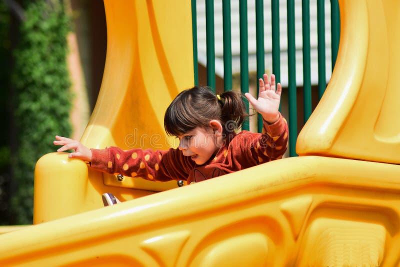 Weinig ongehoorzaam meisje die op de Speelplaats in het stadspark spelen stock fotografie