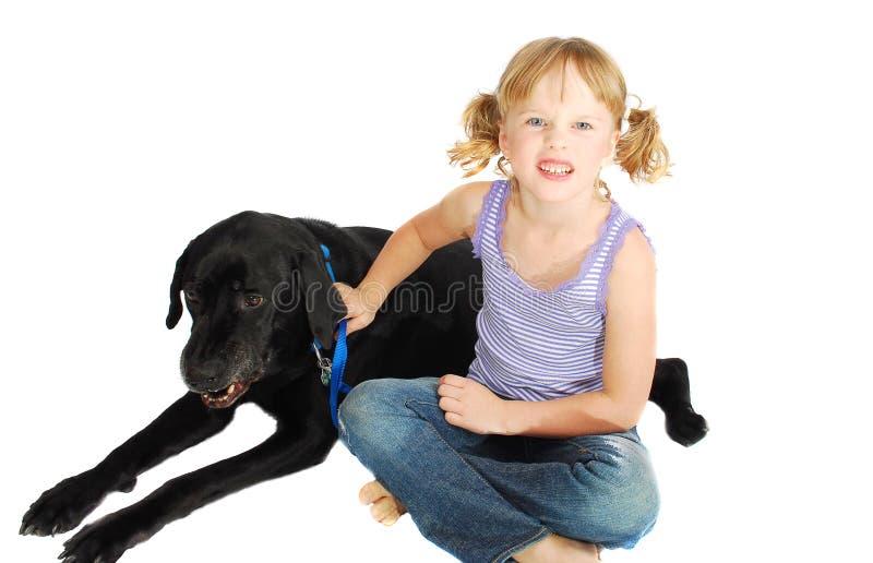 Weinig ongelukkig meisje dat haar agressieve hond opleidt stock foto