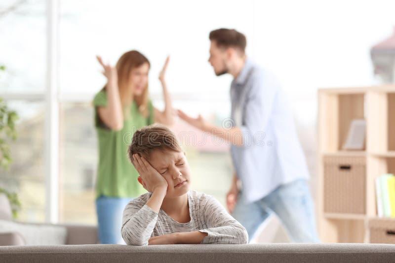 Weinig ongelukkige jongenszitting op bank terwijl ouders royalty-vrije stock fotografie