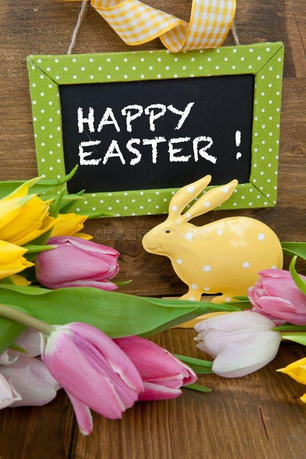 Weinig Pasen-konijntje en kleurrijke tulpen stock afbeelding