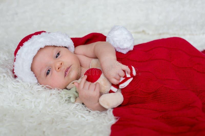 Weinig pasgeboren babyjongen, die Kerstmanhoed dragen royalty-vrije stock fotografie