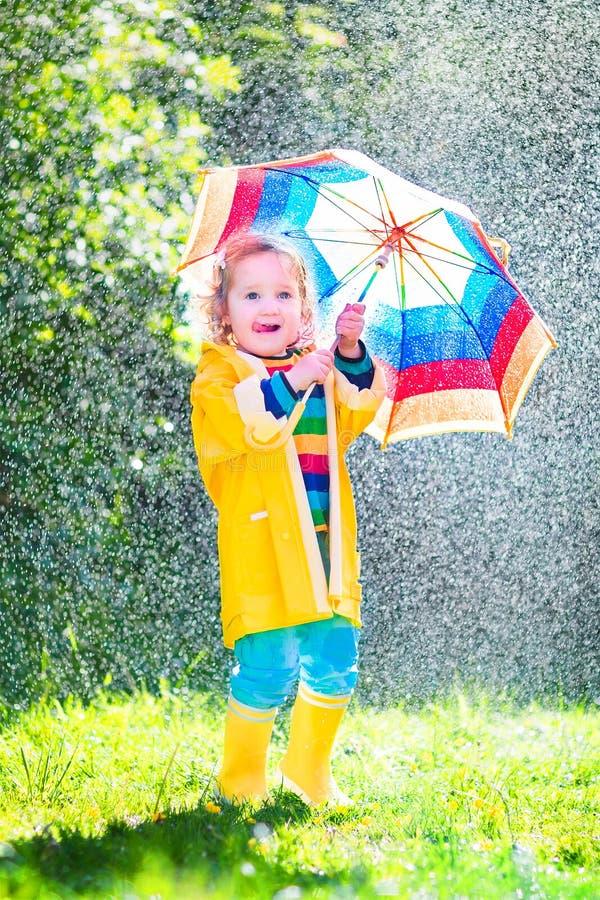 Weinig peuter met het kleurrijke paraplu spelen in regen stock afbeelding