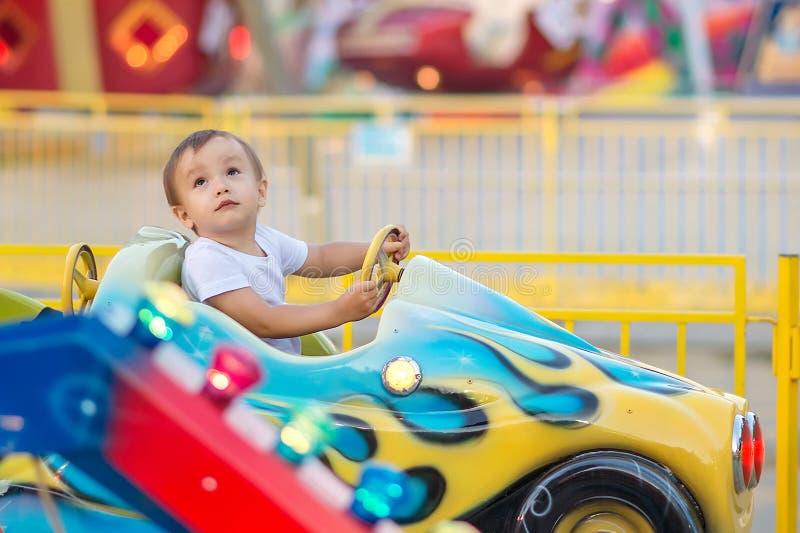 Weinig peuter in themapark: een jongen in wit overhemd die weinig auto berijden op vrolijk gaat rond, helder vermaak op achtergro stock foto
