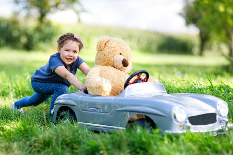 Weinig peuterjong geitjemeisje die grote stuk speelgoed auto drijven en pret met het spelen met groot pluchestuk speelgoed hebben royalty-vrije stock afbeeldingen