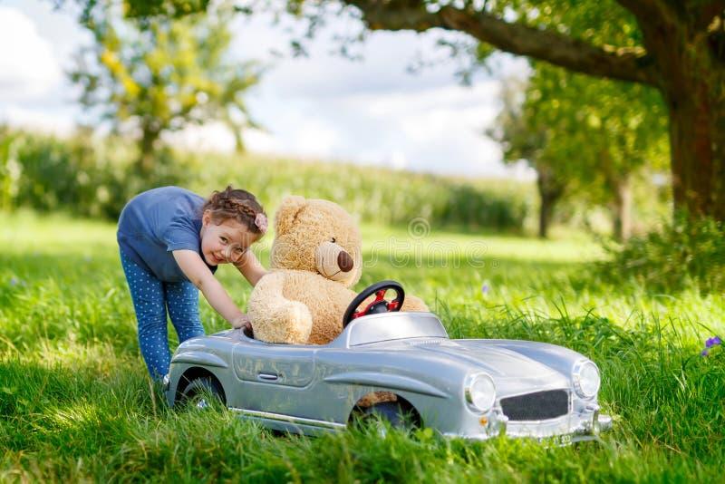 Weinig peuterjong geitjemeisje die grote stuk speelgoed auto drijven en pret met het spelen met grote pluchestuk speelgoed bea he royalty-vrije stock foto