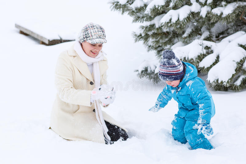 Weinig peuterjongen en zijn moeder die met eerste sneeuw in p spelen stock foto