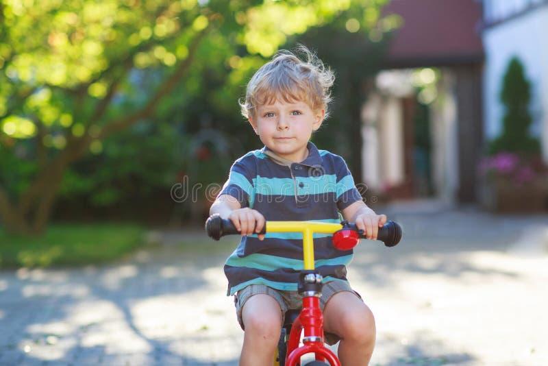 Weinig peuterjongen van 3 jaar die pret op zijn fiets hebben stock afbeeldingen