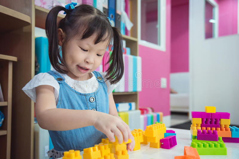 Weinig peuterleeftijdsmeisje die plastic blokken spelen stock fotografie