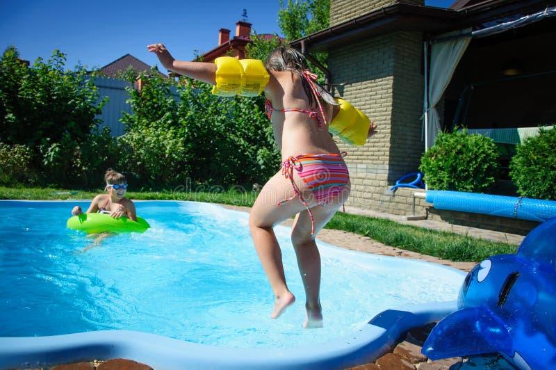 Weinig pretmeisje is zwembad stock foto's