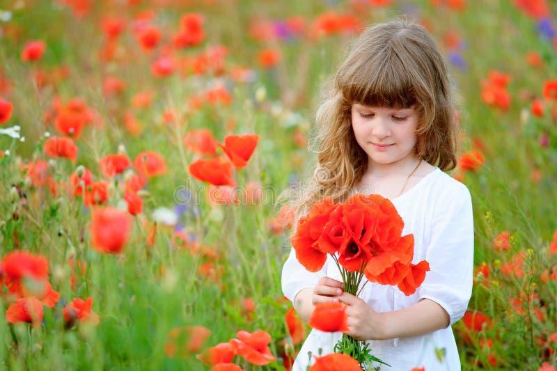 Weinig prinses met wilde rode bloemen op het gebied stock fotografie