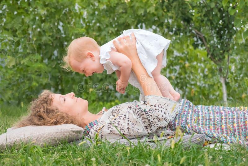 Weinig prinses openlucht spelen Babymeisje op moeder` s handen Glimlachende peuter met moeder Het concept van het het levensbegin royalty-vrije stock foto's
