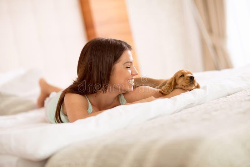 Weinig puppy en zijn eigenares genieten van in bed royalty-vrije stock foto