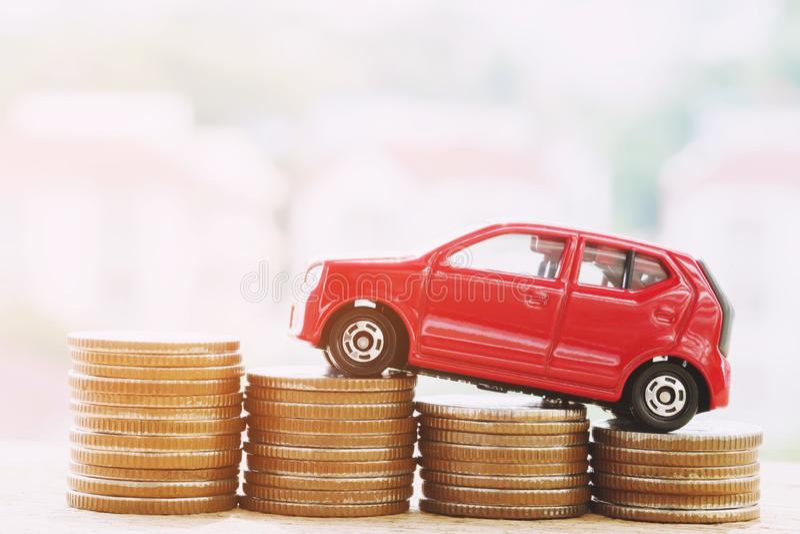 Weinig rode auto over heel wat geld stapelde muntstukken royalty-vrije stock afbeeldingen